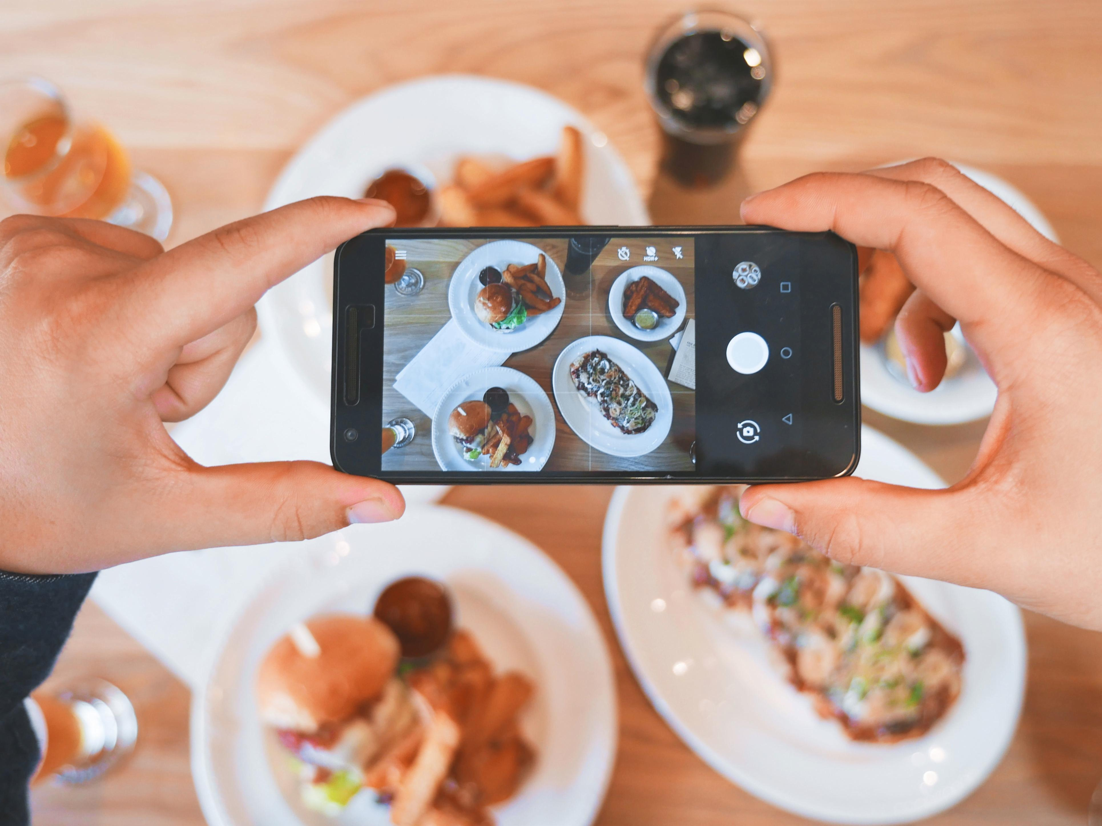 Person taking photo of breakfast with phone showing Instagram's newest feature