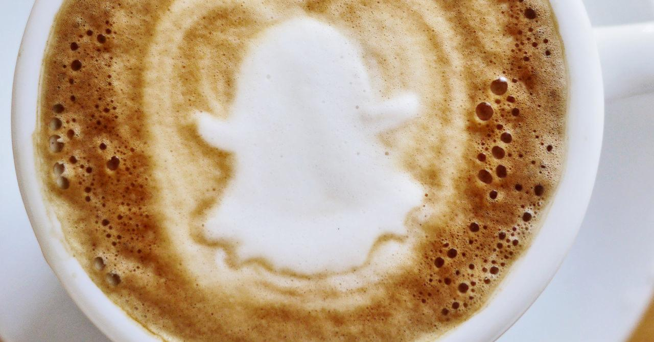 A latte with the snapchat logo in the foam