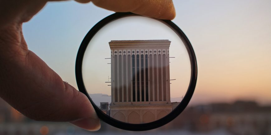 A magnifying glass looking at a building making it look small